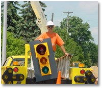 Public worker prepares to install a signal light.