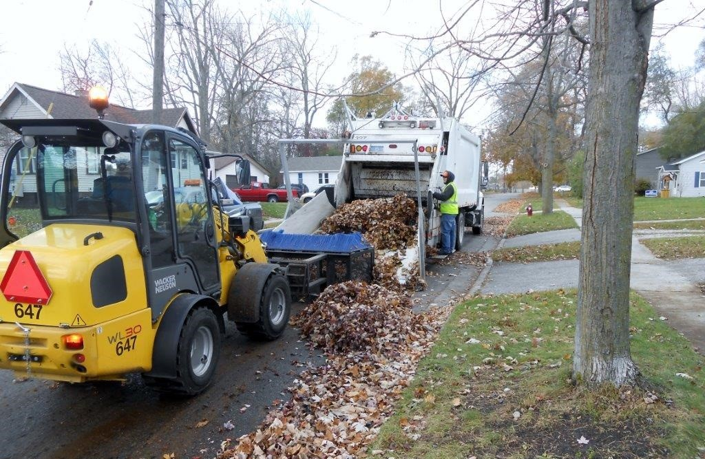Image of two trucks picking up residential leaf piles