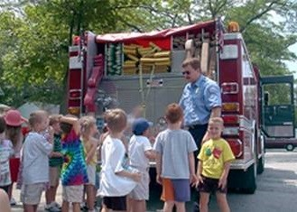 Children being taught fire safety in front of a fire engine
