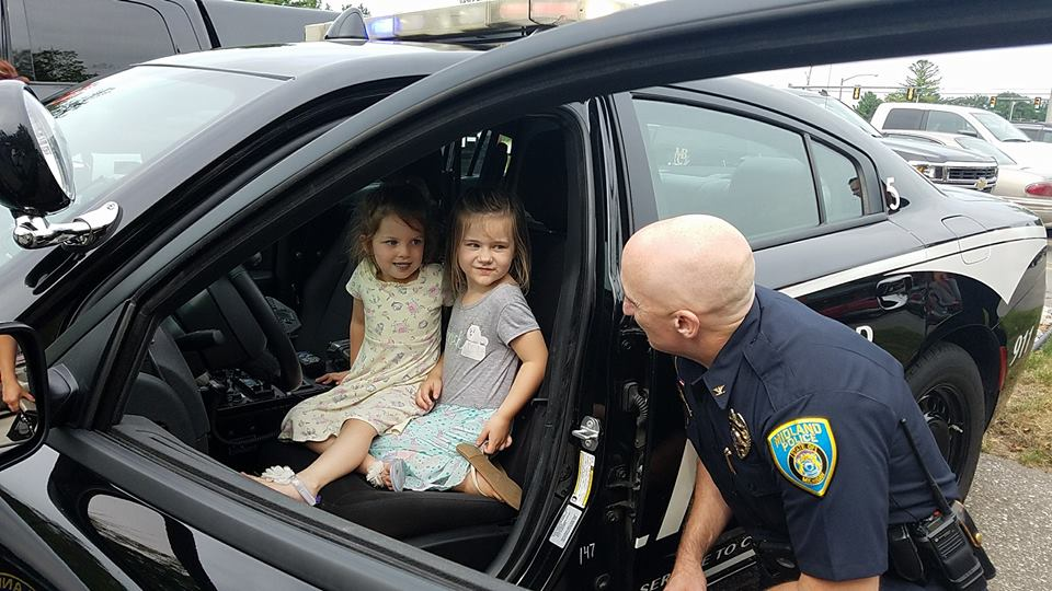 Image of an officer looking into a vehicle with two little girls sitting in a car