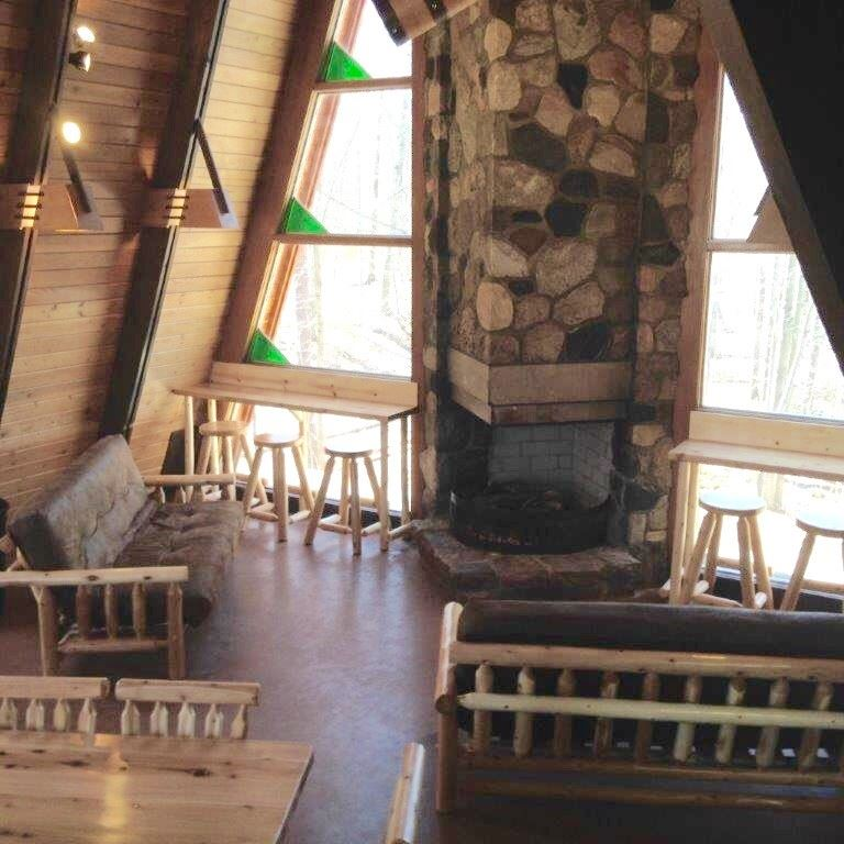 Image of the interior of a chalet with tables and chairs