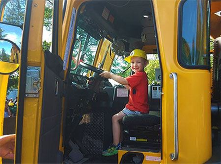Little boy in hardhat sitting in City of Midland trash truck