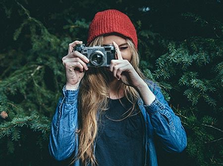 A woman in a red hat taking a picture
