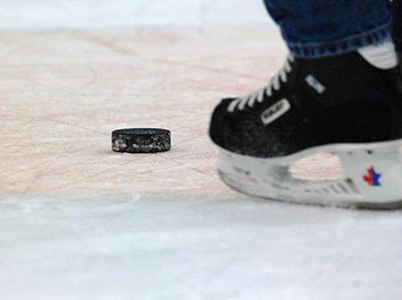 A hockey puck and an ice skate on ice