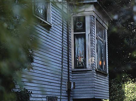 A scary dark house with trees and lights in the window