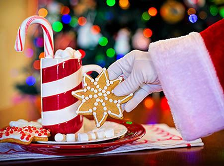 Santa Claus' white gloved hand with a glass of cocoa and a cookie