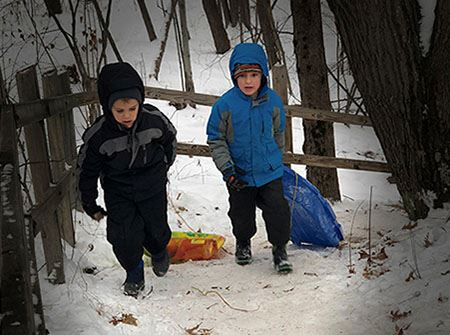 Two boys in winter coats pull sleds up a snowy hill at City Forest
