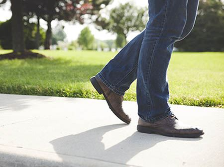 A man&#39s legs and feet walking on a sidewalk