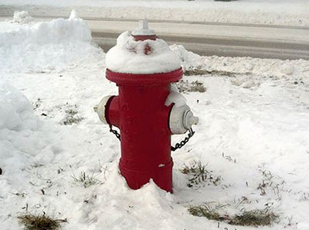 A red fire hydrant with snow around it