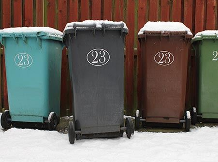 Four trash cans sitting in snow