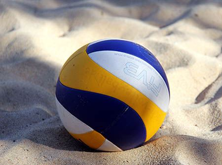 A blue, white, and yellow volleyball on sand
