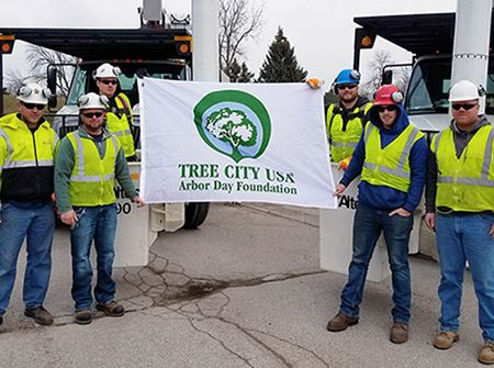 City workers in yellow safety vests holding a white flag that says &#34Tree City USA&#34
