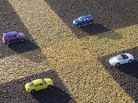 4 toy cars parked in a square around yellow lines in a parking lot