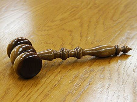 A brown wooden gavel sits on a wooden table