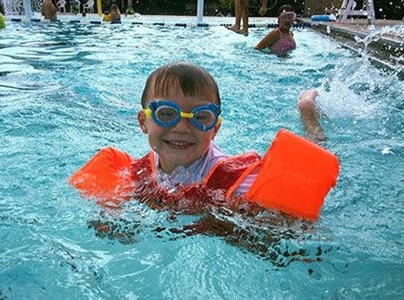 A little boy wearing goggles and orange floaties swims in blue water