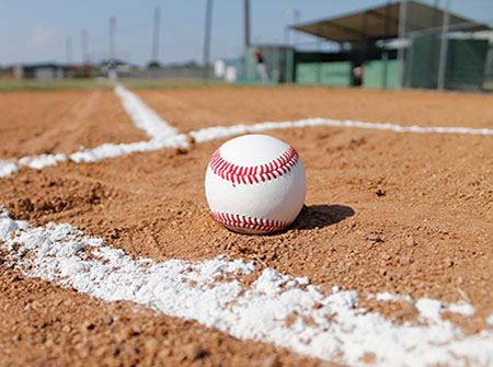 A baseball sits at home plate in a red dirt field