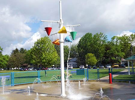 A white pole with red, yellow, and blue buckets dumps water out