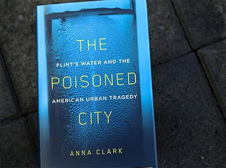"A cover photo of the book ""The Poisoned City"" on concrete"