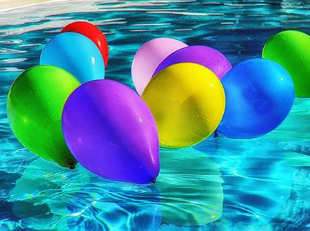 A bright blue pool with red, blue, orange, and yellow ballons