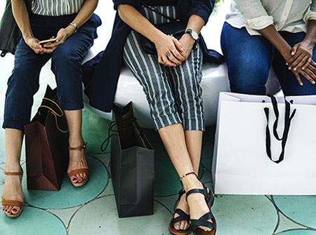 Three women sit on a bench in sandals with shopping bags at their feet