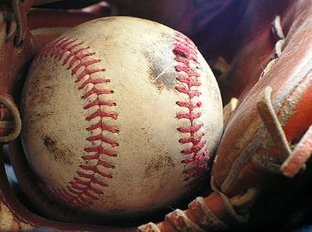 A white dirty baseball sits in an old brown baseball mitt