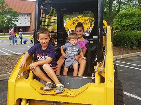 Three children sit in the seat of a yellow earth mover