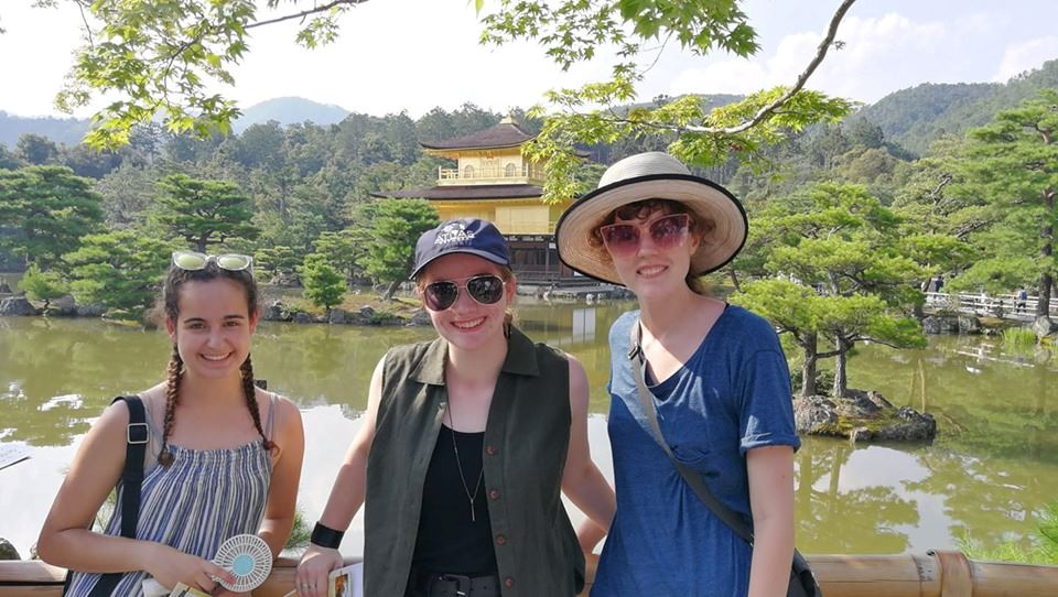Three Midland high school girls stand in front of a Japanese temple