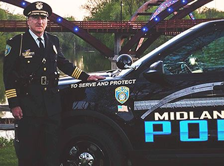 Police Chief Cliff Block in front of the Tridge with a cruiser
