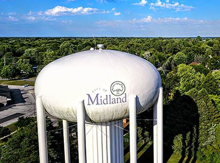A white water tower over green trees in a blue sky