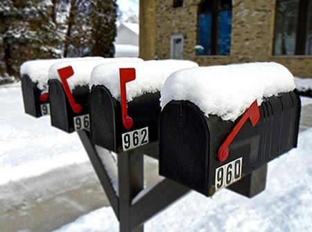 A row of black mailboxes with red flags covered in snow