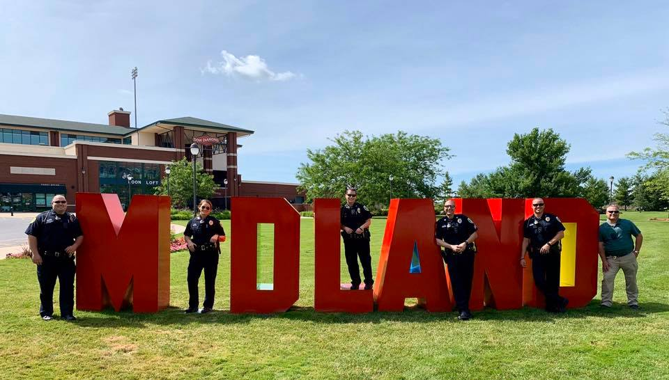 A group of police officers stand with red letters spelling out Midland
