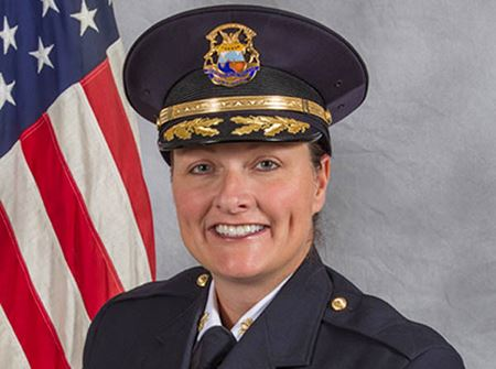A white female police chief with a blue hat on a gray background with a US flag