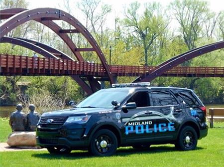A black MPD SUV sits on green grass in front of the Tridge on a sunny day