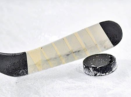 A hockey stick on white ice with a black puck