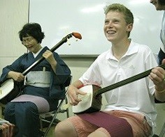 A Midland student plays a different, stringed instrument during his stay in Japan.