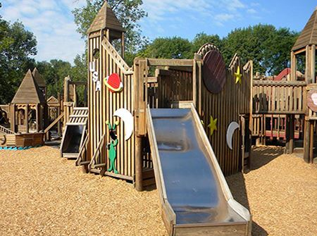 A playground made of wood with a metal slide and a blue sky