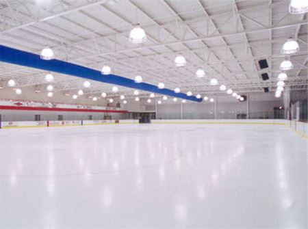 A white ice rink with blue lines and boards