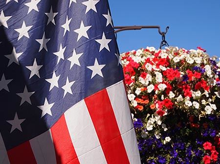 An American flag hangs on a pole next to a basket of red, white, and blue flowers.