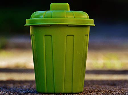 A small green refuse can