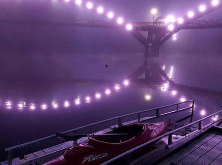 A red kayak sits in the river under the purple lights of the Tridge