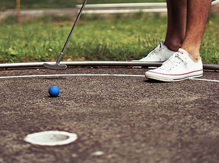 A woman putts a blue golf ball into a hole