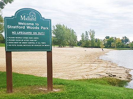 Stratford Woods Park beach including a beach, green sign, and a lake