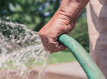 A white man holds a green garden hose that sprays water