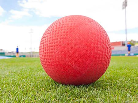 A red kickball sits on green grass