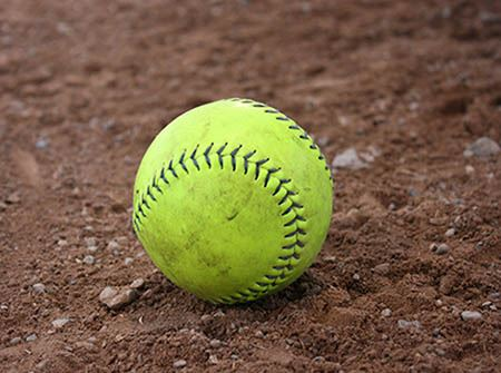 A bright green softball sits on a brown dirt baseball field