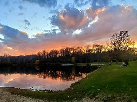 A lake with a pink, orange, and blue sunset over woods