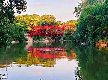 A red bridge at sunset over a river with green trees around