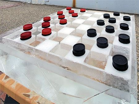 Black and red checkers sit on a checkerboard made of ice