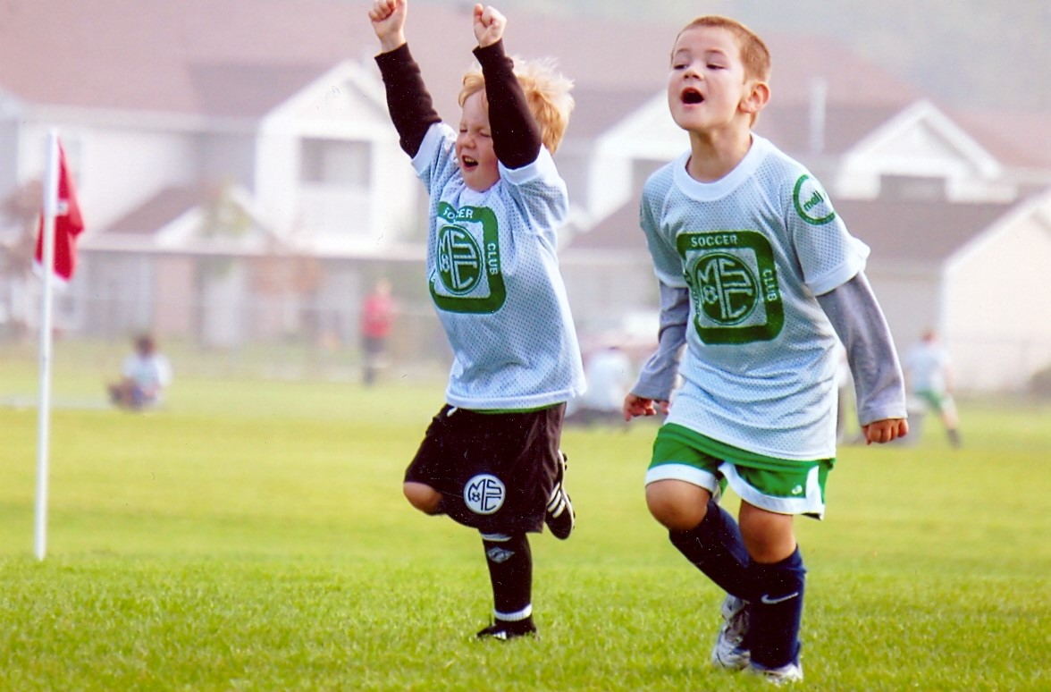 Two children cheering in soccer uniforms on field