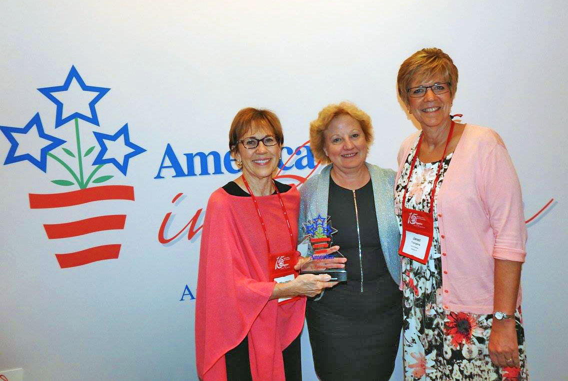 Mayor Maureen Donker and Assistant Director of Public Services Jan Yuergens pose with Midland's America in Bloom trophy